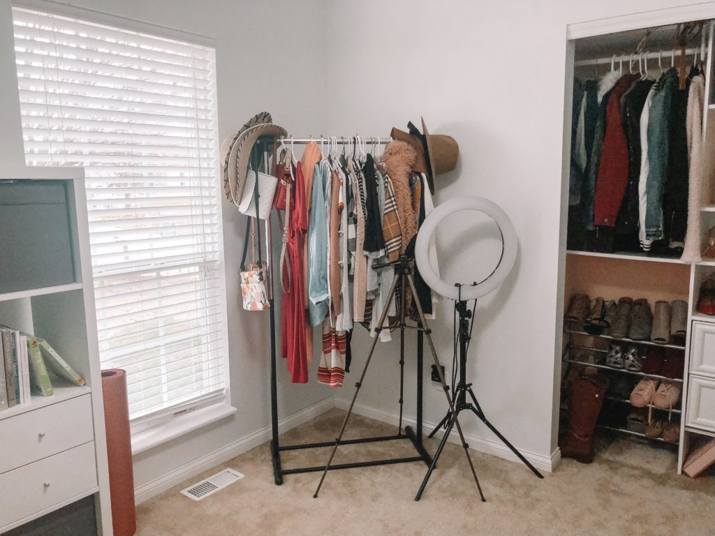 clothing rack by window with lights and camera tripod