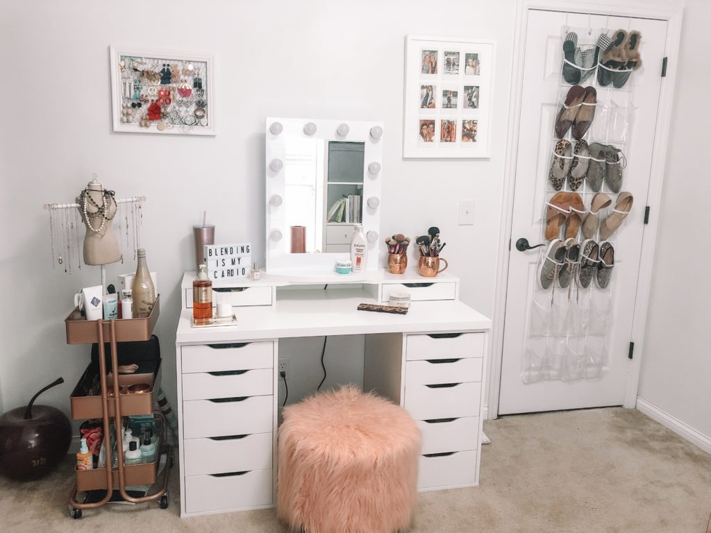 Beauty vanity with fluffy pink chair and makeup drawers.