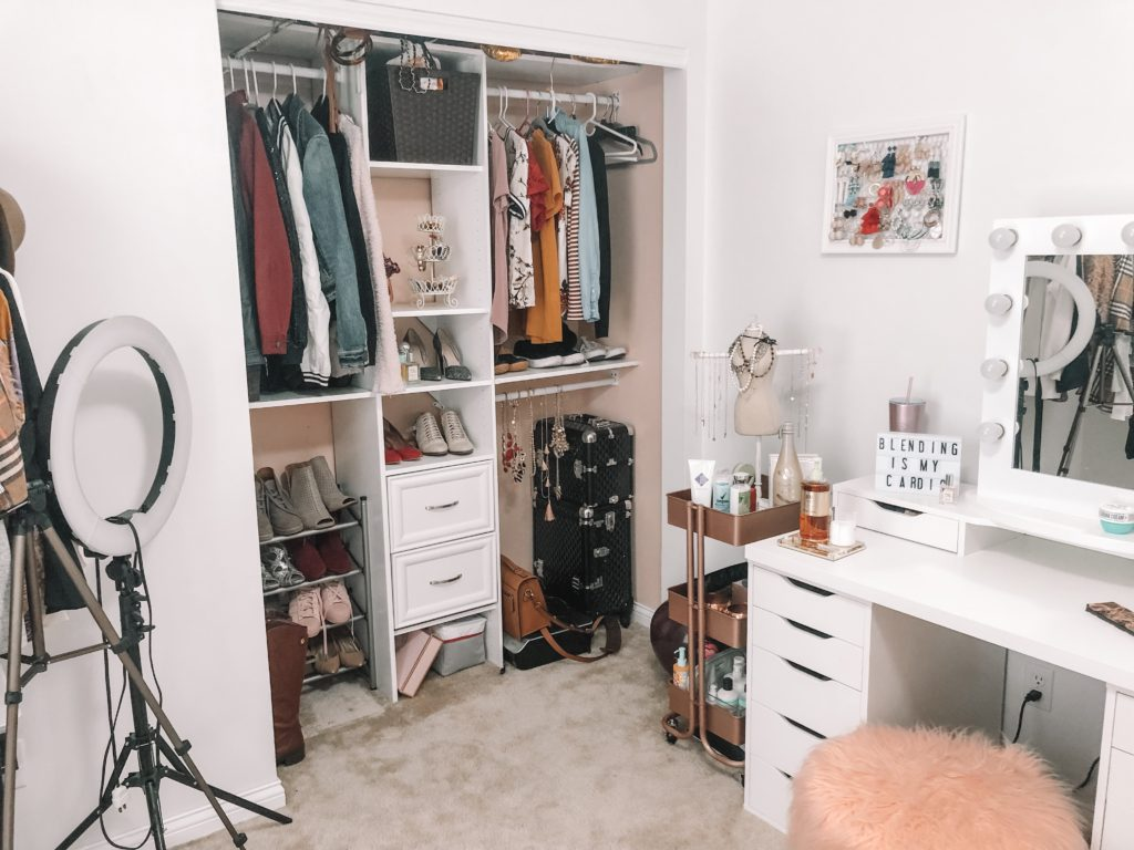 Open closet with vanity and three tier cart in corner