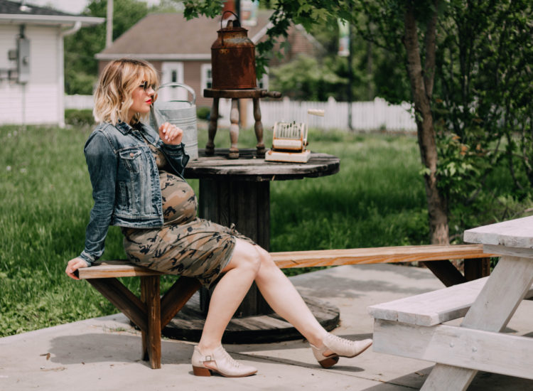 Taylor sitting on bench in camo dress