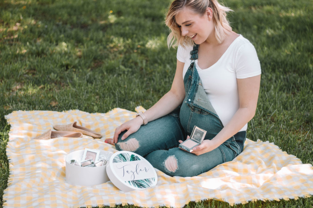 Taylor sitting on a picnic blanket with a box of makeup powders
